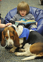 NWA Democrat-Gazette/Michael Woods --01/14/2015-- w @NWAMICHAELW... Gabriel Stewart, age 4 from Springdale, reads a book to Banjo, a therapy dog, during Wednesday evenings session of the Kibbles and Books program at the Springdale Public Library. Kibbles & Books is a literacy program designed to build confidence in young readers by reading out loud to therapy dogs giving the children a chance to practice their literacy skills in a stress-free and fun context.