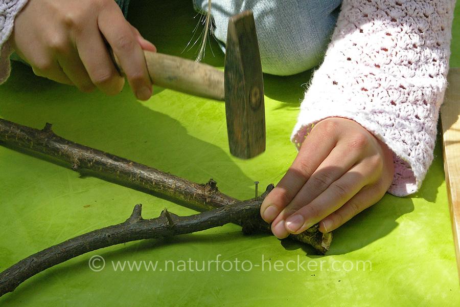 Kinder weben ein Blumenbild, Mädchen legt einen Rahmen aus Ästen und nagelt ihn an den Ecken zusammen