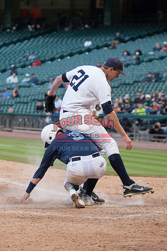 Rice Owls starter Austin Kubitza #21 is upended by North Carolina baserunner Mike Zolt #3 in the second inning  during the NCAA baseball game against the North Carolina Tar Heels on March 1st, 2013 at Minute Maid Park in Houston, Texas. North Carolina defeated Rice 2-1. (Andrew Woolley/Four Seam Images).