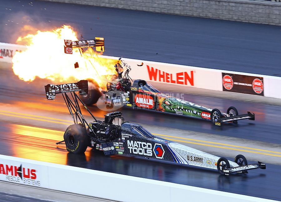 Sep 20, 2015; Concord, NC, USA; NHRA top fuel driver Antron Brown (near) races alongside Terry McMillen explodes an engine on fire during the Carolina Nationals at zMax Dragway. Mandatory Credit: Mark J. Rebilas-USA TODAY Sports