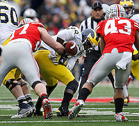 Ohio State Buckeyes defensive lineman Joey Bosa (97) forces Michigan Wolverines quarterback Devin Gardner (98) to fumble the ball during the 4th quarter of the NCAA football game at Ohio Stadium on Nov. 29, 2014. Ohio State Buckeyes linebacker Darron Lee (43) returned the fumble for a touchdown. (Adam Cairns / The Columbus Dispatch)