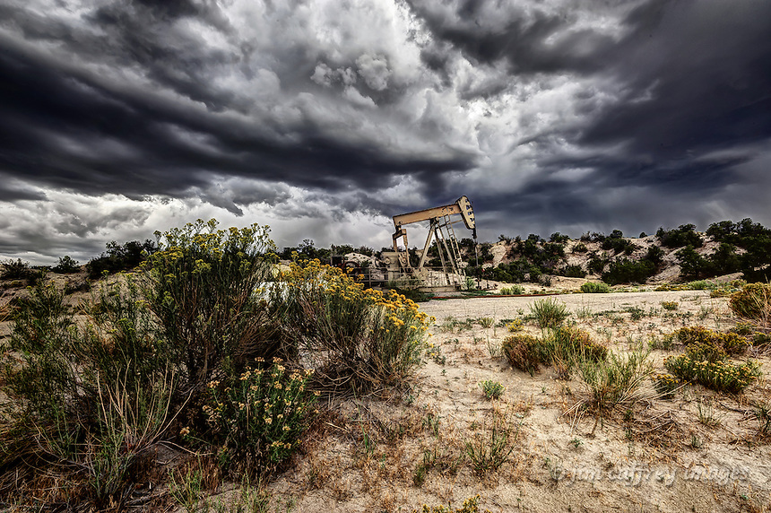 A gas well in the middle of the Lybrook badlands in the San Juan Basin with chamisa growing in the foreground