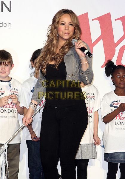 MARIAH CAREY.turns on the Christmas Lights at Westfield Shopping Centre, London, England, UK, November 19th 2009..half length microphone black grey gray cropped jacket knitted top jeans trousers silver bracelets  smiling  wand  holding speaking .CAP/ROS.©Steve Ross/Capital Pictures.