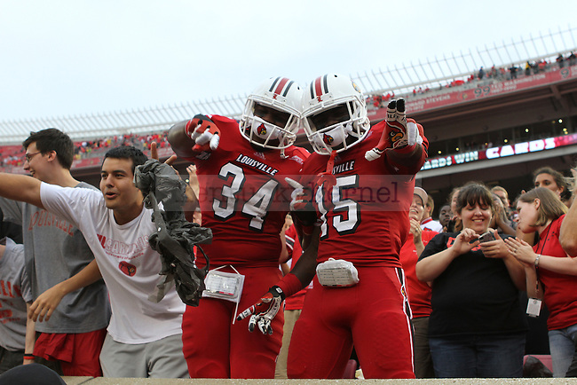 The University of Louisville football teammates George Durant and Andrew Johnson celebrate after winning the Governor's Cup on Sunday, Sept. 2, 2012 in Papa John's Stadium in Louisville, Ky. Louisville won 32-14. Photo by Latara Appleby | Staff