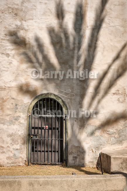 Barred doorway, palm shadow, Mission San Gabriel Arcángel, forth of the 21 California Missions and founded by Father Junipero Serra, September 8, 1771.
