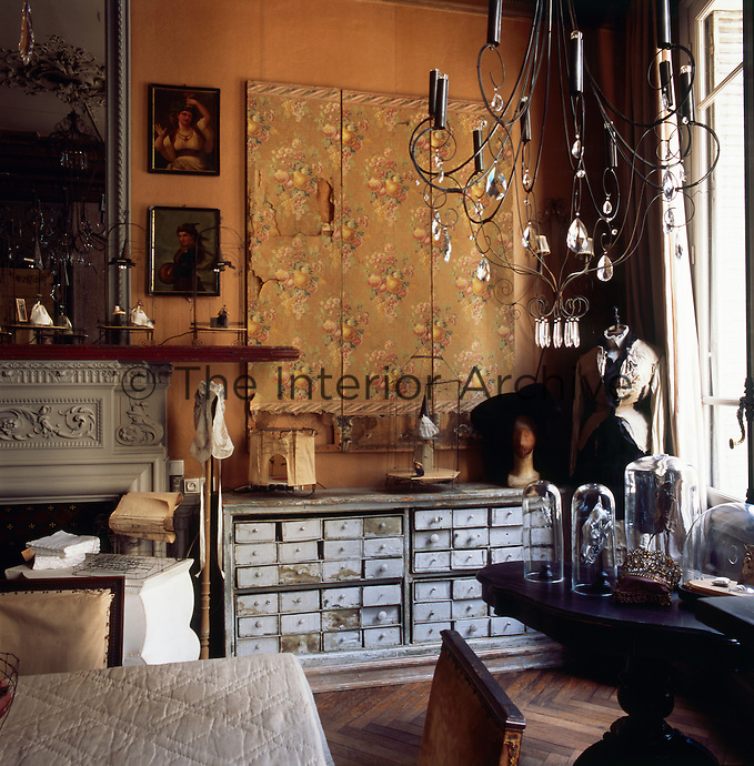 A tailor's dummy stands in the corner of a traditional living room dressed in old fashioned style clothing. The room has an ornate fireplace and is furnished with an eclectic mix of furniture.