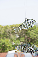 Hand-painted glass fish are suspended on fishing line on the covered terrace