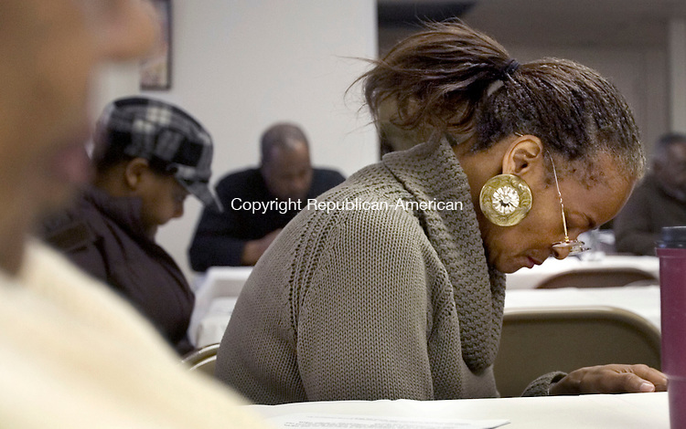 TORRINGTON, CT. 14 January 2012-011412SV05-DeLois Lindsey of Torrington bows her head in prayer during the Martin Luther King breakfast hosted by the AME Zion Church in Torrington Saturday..Steven Valenti Republican-American