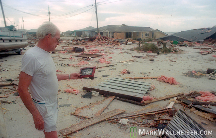 70 year-old John Hays looks at a family photo on Gulf Drive in Panama City Beach, Florida after Hurricane Opal impacted the Florida panhandle as a category three storm when it came ashore near Pensacola, Florida October 5, 1995.  It was the strongest hurricane of the 1995 season and killed 63 people, 13 in the United States.  Hurricane Opal's name was retired the following year.