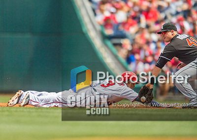 14 May 2016: Washington Nationals outfielder Michael Taylor dives safely back to first as Miami Marlins first baseman Justin Bour catches the pick-off attempt during the first game of a double-header against the Miami Marlins at Nationals Park in Washington, DC. The Nationals defeated the Marlins 6-4 in the afternoon matchup.  Mandatory Credit: Ed Wolfstein Photo *** RAW (NEF) Image File Available ***