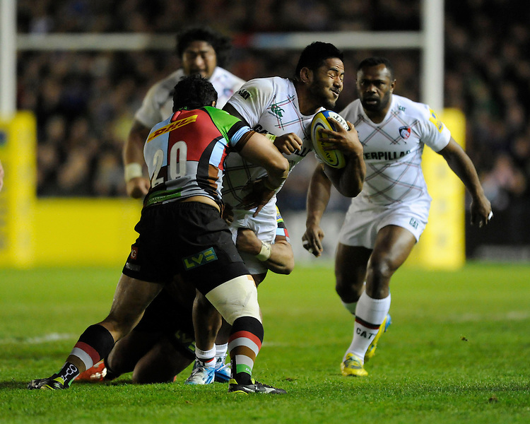 Manusamoa Tuilagi of Leicester Tigers is tackled by Maurie Fa'asavalu and Jordan Turner-Hall of Harlequins during the Aviva Premiership match between Harlequins and Leicester Tigers at the Twickenham Stoop on Friday 18th April 2014 (Photo by Rob Munro)