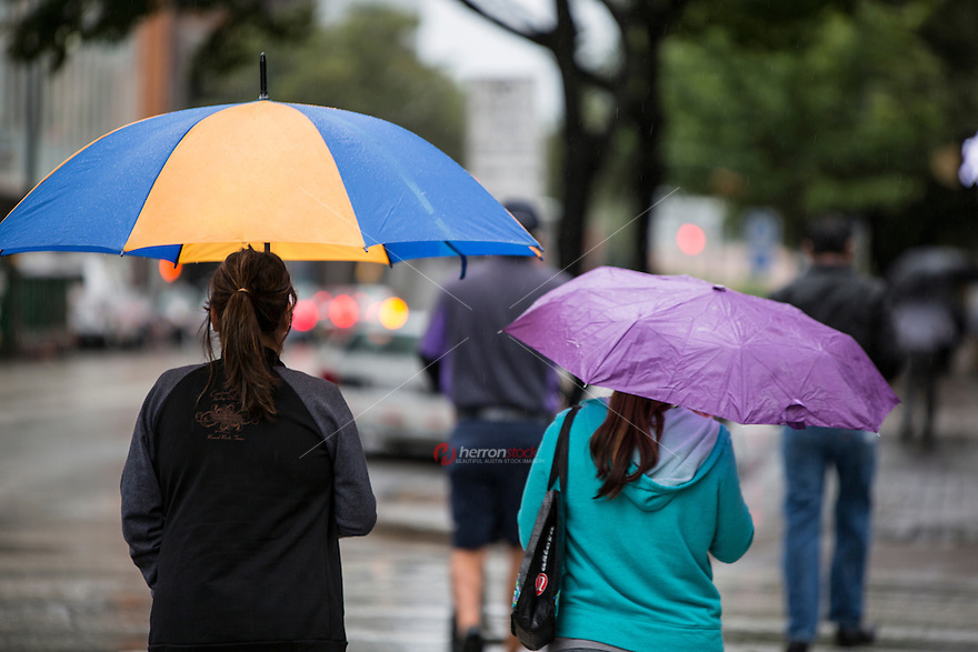 Rainy day as downtown workers hold umbrellas to shield from the spring showers in downtown Austin, Texas, downtown business district.