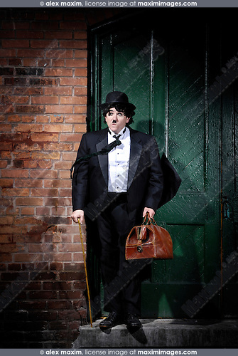 Charlie Chaplin mime Businessman in black suit down-and-out standing at a closed door on the street in a spot of light with stupefied dramatic expression and his clothes fluttering in the wind. Artistic humorous concept. Performing artist Peter Jarvis.