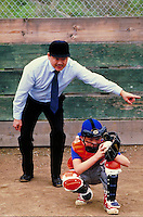 UMPIRE AND YOUNG CATCHER AT DIAMOND. BASEBALL UMPIRE AND CATCHER. OAKLAND CALIFORNIA USA.