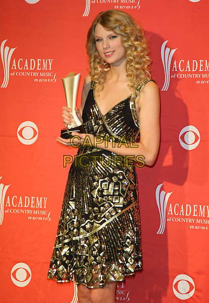 TAYLOR SWIFT.Pressroom at the 44th Annual Academy Of Country Music Awards held at the MGM Grand Garden Arena, Las Vegas, Nevada, USA..April 5th, 2009.half length black gold beads beaded dress award trophy .CAP/ADM/MJT.© MJT/AdMedia/Capital Pictures.