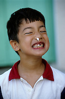Six year old boy with a missing tooth making a silly face, France.