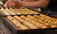 Chef Ryota Akai of Japan turns takoyaki during a demonstration of takoyaki cooking at Mitsuwa Market in Costa Mesa, California.  The takoyaki in front are almost finished and looking nicely browned, while the batch in back has just been rolled into balls.