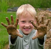 Lehmbackofen im Schulgarten, Garten der Grundschule Nusse wird als Projektarbeit von einer 1. Klasse gestaltet, Junge zeigt begeistert seine lehmigen Hände, Gartenarbeit