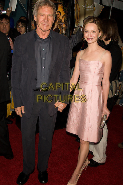 "HARRISON FORD & CALISTA FLOCKHART.Premiere of ""Indiana Jones and the Kingdom of the Crystal Skull"" in Harlem.at the AMC Magic Johnson Theaters, Harlem, NY, USA..May 20th, 2008 .full length black grey gray suit holding hands pink satin dress couple .CAP/LNC/TOM.©TOM/LNC/Capital Pictures."