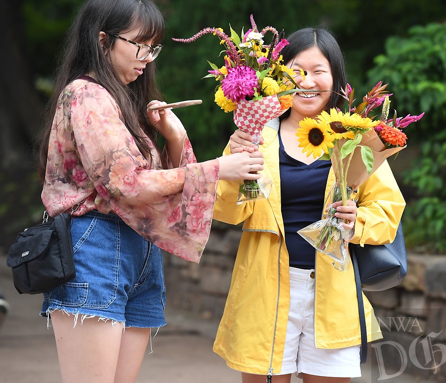 NWA Democrat-Gazette/J.T. WAMPLER  Anna Moriarty (LEFT) hands her flowers to her friend Cadi Stair ((CQ)) of Fayetteville Thursday August 8, 2019 at the Fayetteville Farmers Market. Moriarty is visiting from Texas. This week is National Farmers Market Week. There are farmers markets Bella Vista on Sundays, Fayetteville and Springdale on Tuesdays, Thursdays and Saturdays, and in Bentonville and Rogers on Saturdays.