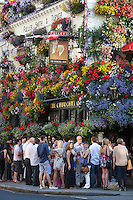 Great Britain, London, Kensington and Chelsea: After work drinkers outside flower decked The Churchill Arms pub on Kensington Church Street | Grossbritannien, England, London, Kensington and Chelsea: auf ein Bier nach getaner Arbeit -The Churchill Arms blumengeschmueckter Pub an der Kensington Church Street