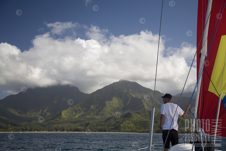 Young man standing on the bow of a cruising sailboat approaching Hanalei Bay, with Namolokama Mountain in the background