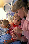mother checking temperature on oral thermometer of sad sick young girl in bed with her doll