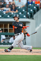 Christian Walker (22) of the Norfolk Tides follows through on his swing against the Charlotte Knights at BB&T BallPark on July 17, 2015 in Charlotte, North Carolina.  The Knights defeated the Tides 5-4.  (Brian Westerholt/Four Seam Images)