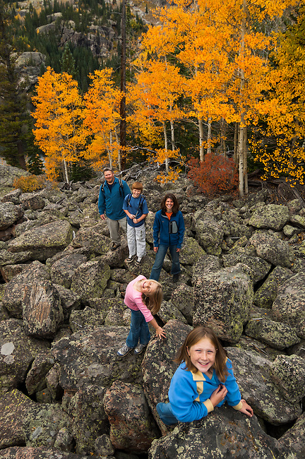Family pauses for photo after scramble over boulders with golden colors of autumn in aspen stands above, all on a September morning above Bear Lake in Rocky Mountain NP, Colorado/ (MR)#86