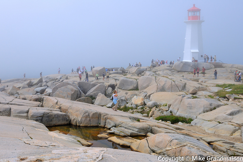 Lighthouse and rocky shoreline  in fog<br /> Peggy's Cove<br /> Nova Scotia<br /> Canada