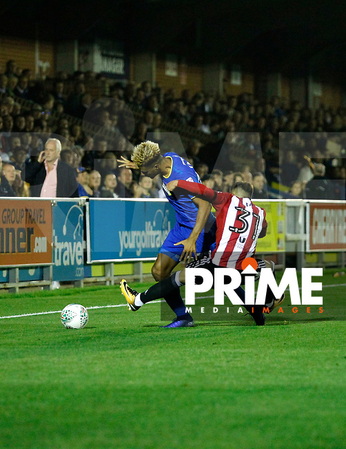 AFC Wimbledon's Lyle Taylor tussles with Brentford's Ilias Chatzitheodoridis during the Carabao Cup match between AFC Wimbledon and Brentford at the Cherry Red Records Stadium, Kingston, England on 8 August 2017. Photo by Carlton Myrie.