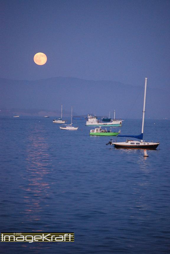 Moon reflecting on water at dusk with boats in Santa Barbara harbor