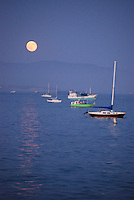 Moon reflecting on water at dusk with boats in Santa Barbara harbor
