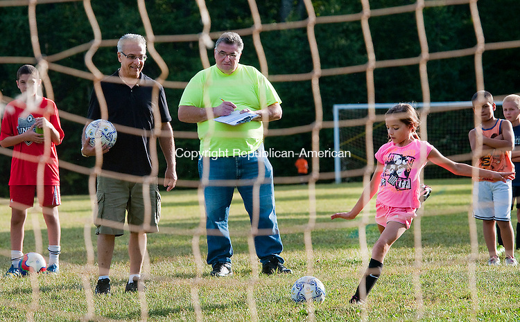 PLYMOUTH, CT 091014JS01--<br /> Julianna Lloret, 9, takes a shot on goal as Joseph Consorte, Grand Knight for the Knights of Columbus Council 1090 of Terrryville left, and Mike Mikulskis, Inside Guard at the Knights of Columbus, look on during the annual Knights of Columbus Soccer Challenge held Wednesday at Fisher Elementary School in Plymouth. Nearly 20 children between the ages of 9-14, tested their skills with winners in each age division, moving to the next round through district and state competitions. <br /> Jim Shannon Republican-American