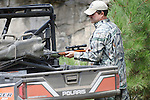 Hunter with rifle and Polaris Ranger
