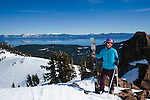 Woman walking along the high traverse while spring skiing at Alpine Meadows ski resort, California, with Lake Tahoe in the background.