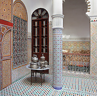 Corner of the ground floor central courtyard with zellige tile decoration, painted door panels and a table set with silver tea ware, in a typical Tetouan riad, a traditional muslim house built around a courtyard, built in Moorish style with strong Andalusian influences, next to the Great Mosque or Jamaa el Kebir in the Medina or old town of Tetouan, on the slopes of Jbel Dersa in the Rif mountains of Northern Morocco. Tetouan was of particular importance in the Islamic period from the 8th century, when it served as the main point of contact between Morocco and Andalusia. After the Reconquest, the town was rebuilt by Andalusian refugees who had been expelled by the Spanish. The medina of Tetouan dates to the 16th century and was declared a UNESCO World Heritage Site in 1997. Picture by Manuel Cohen