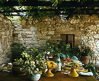 A simple wooden table laid for lunch in the shade of an overgrown arbour