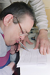 Man with Cerebral Palsy signing form with pen in mouth.  MR