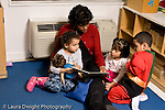 Education preschool 4 year olds books and reading female teacher sitting and reading to group two girls and a boy horizontal