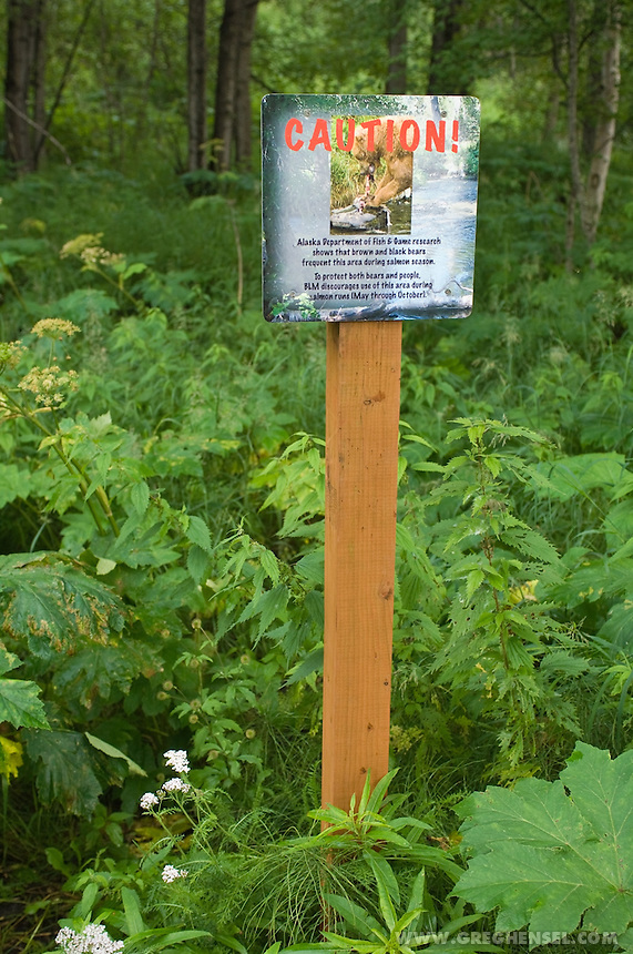 A sign warns visitors of bear activity on a hiking trail in Anchorage . Summer in Southcentral Alaska.