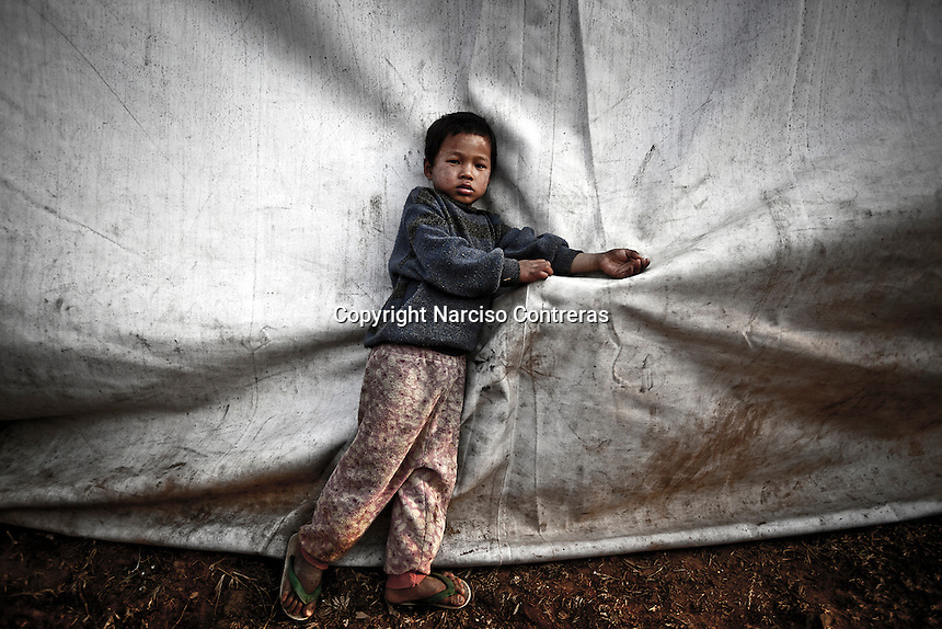 A Kachin refugee child stands out of a tent as he waits for the rice ration given by the WaPaNa NGO at Seng Mai Pa IDP camp, one of the multiple camps settled outskirts of Maiya Jang city. The camp gives shelter to two thousand displaced persons from the war-torn villages in Kachin State.