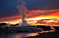 The sun sets over the Firehole River and Midway Geyser Basin in Yellowstone National Park.