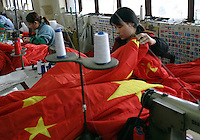 Workers puts the finishing touch on almost completed Chinese national flags at the Shanghai Flag Factory in Shanghai, China. A majority of flags used around the world are produced in China due to its low costs, however state-owned factory like this one are out competed by smaller private firms who are more flexible and cheaper. Unlike many countries around the world, China's laws forbids any private use of its national flag..26-APR-04