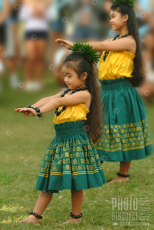 Little girls with kukui nut lei during a hula performance, Hawai'i.