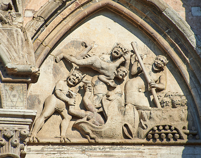 Sculpture from The Last Judgement of sinners being boiled in a cauldren or fed to a monster in hell on the facade of the 12th century Romanesque Ferrara Duomo, Italy