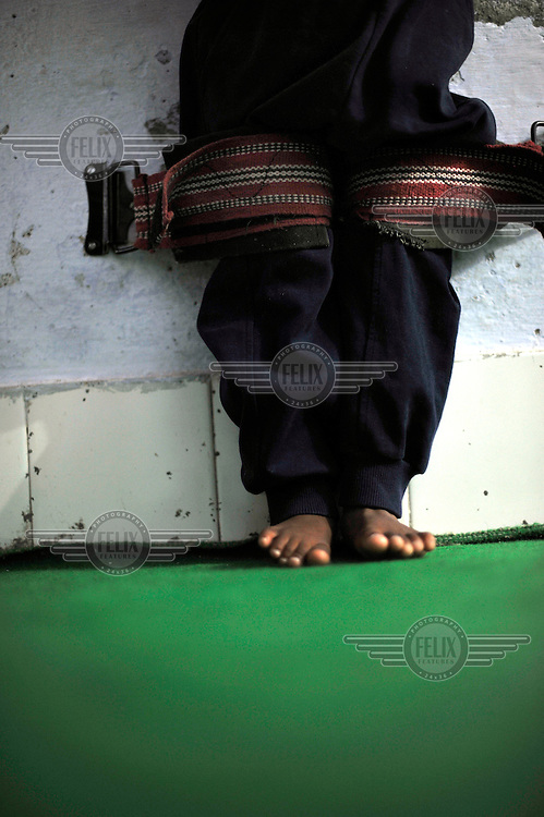4 year old Akriti who has cerebral palsy is strapped to a wall to help straighten his limbs at the privately funded Baba Farid Centre in Faridkot. An increasing and ignored percentage of children are being born suffering the side effects of industrial pollution. The Baba Farid Centre was set up by Dr Pritpal Singh and is staffed on a volunteer basis by his network of similarly concerned fellow junior doctors and specialists. It treats its patients with a mixture of homeopathic, ayurvedic and acupuncture methods.