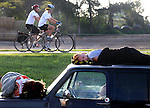 Early morning RAGBRAI riders roll past a few sleepy riders atop a truck in Dyersville.