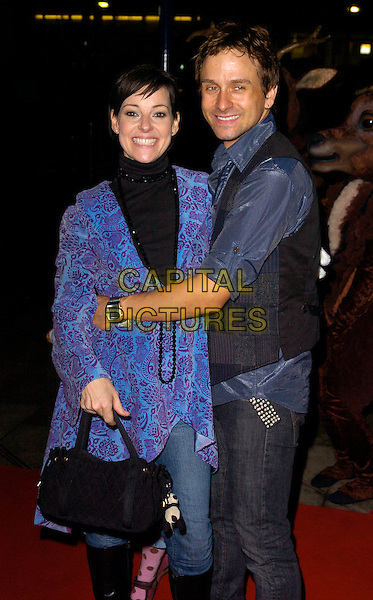 "RUTHIE HENSHALL & husband.""The Snowman"" press night, Peacock Theatre, London, England..December 6th, 2007.half 3/4 length jeans denim black blue paisley purple print pattern necklace top high collar bag purse waistcoat married couple hug embrace arms around waist .CAP/CAN.©Can Nguyen/Capital Pictures"