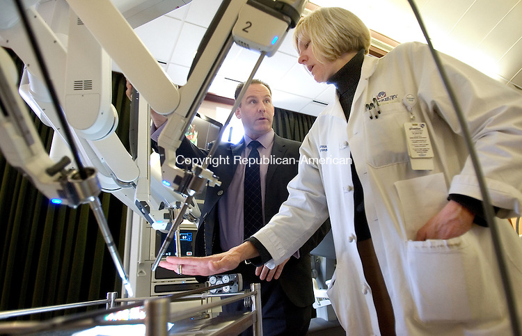 WATERBURY CT. 24 March 2015-032415SV10-From left, Guy Budinscak, da Vinci Clinical Sales Manager, shows Joan Doback, PA-C, a new da Vinci machine during a technology fair at Waterbury Hospital in Waterbury Tuesday. <br /> Steven Valenti Republican-American